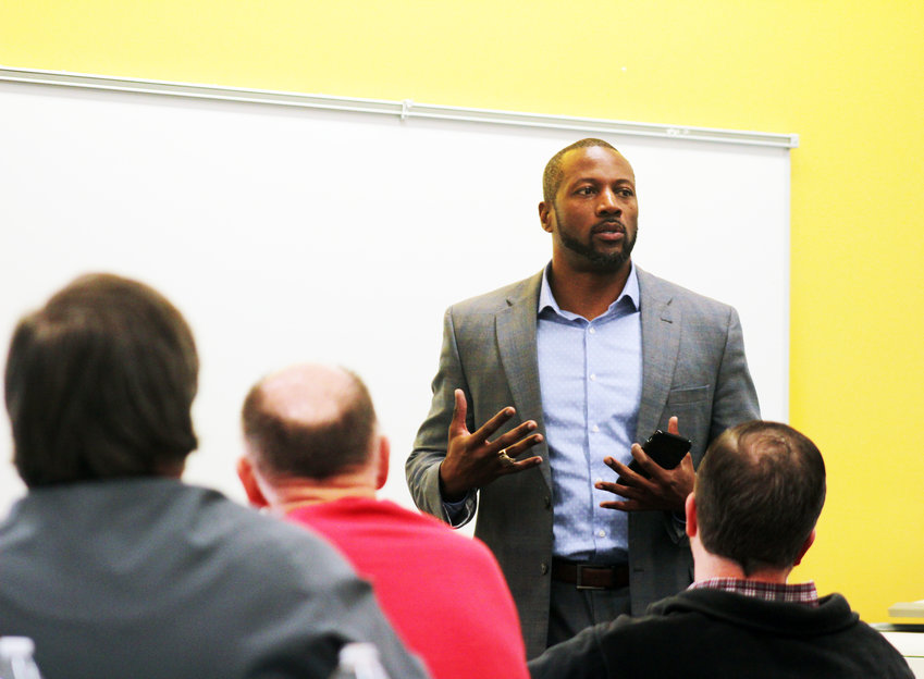 Former Husker football player and current Teammates mentor Tony Veland talks to Blair Teammates mentors at the Blair Library and Technology Center on Thursday.
