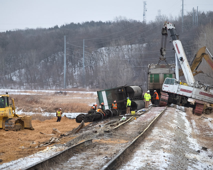 A crew works to remove several train cars that derailed on a rail line belonging to Cargill on Tuesday near the U.S. Highway 75 entrance.