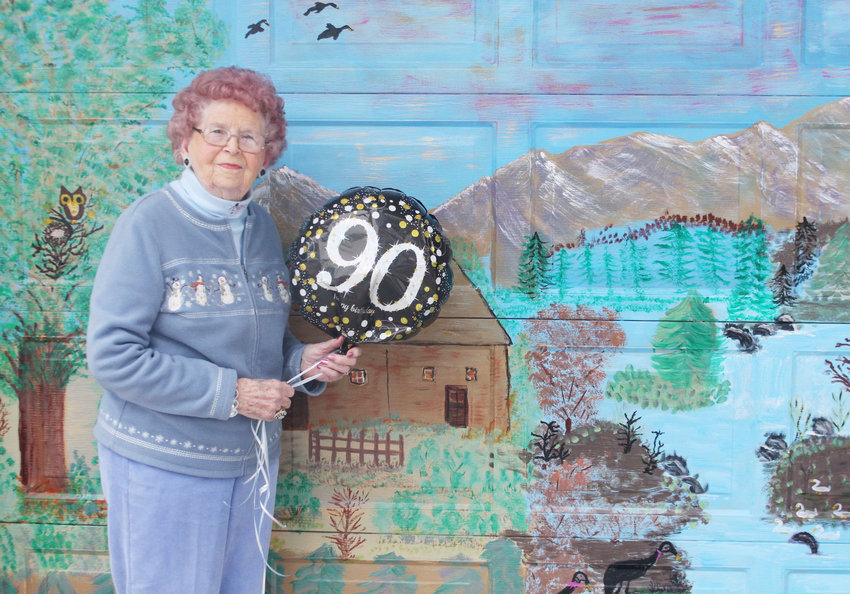 Gloria Jensen stands in front of a mural she painted on her garage door at her home along 17th Street in Blair. Jensen recently turned 90 years old.