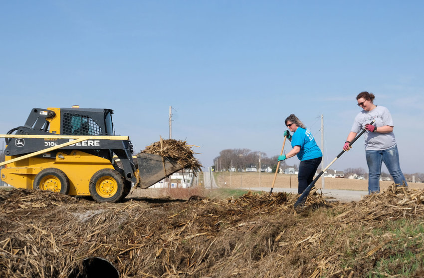 Cher and Ellie Krause rake cornstalks along the edge of a culvert at Bell Creek Park in Arlington in April as part of flood clean up efforts.
