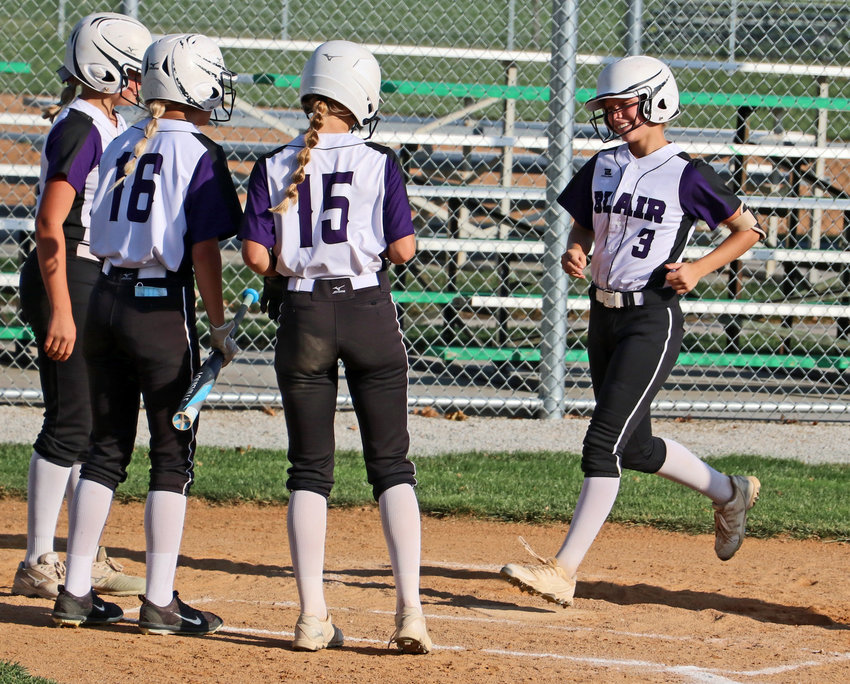 Blair's Jerzie Janning, from left, Julia Saylor and Nessa McMillen welcome Leah Chance back home after the freshman's 3-run homer Tuesday during the Class B Subdistrict 2 Tournament at the Youth Sports Complex.