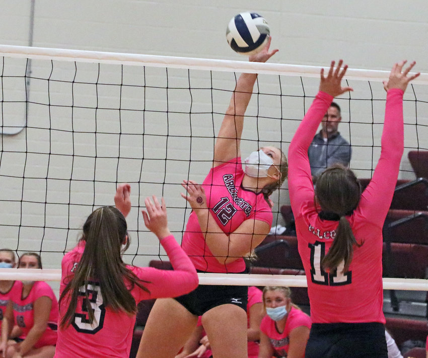 Eagles senior Mallory Ruwe, middle, spikes the ball at the net Thursday against Douglas County West at Arlington High School.