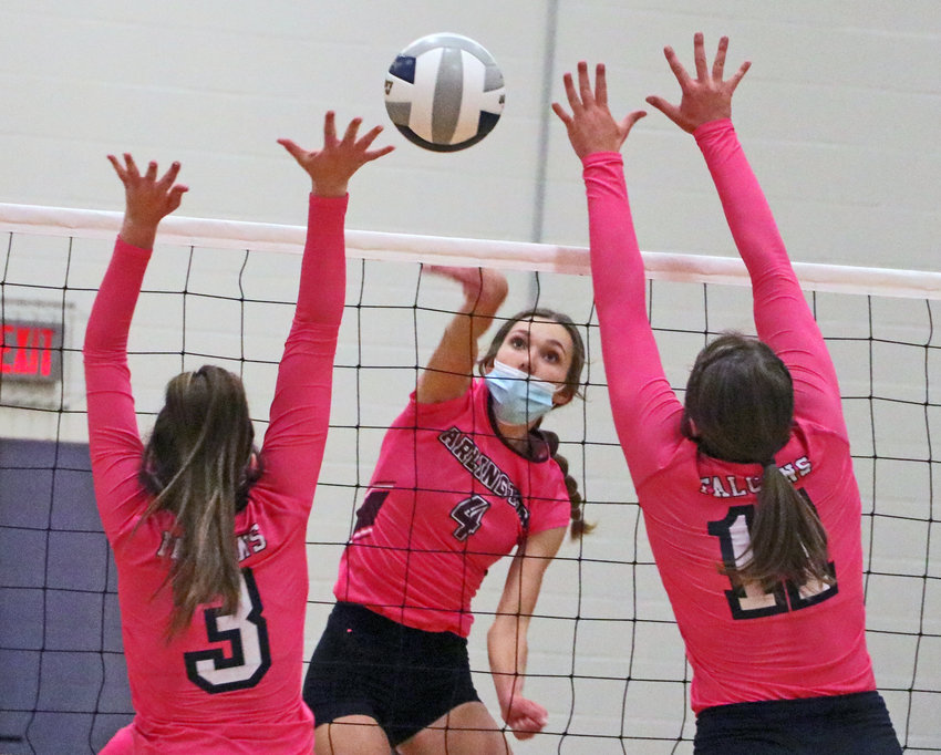 Eagles junior Kailynn Gubbels, middle, spikes the ball Thursday at Arlington High School.