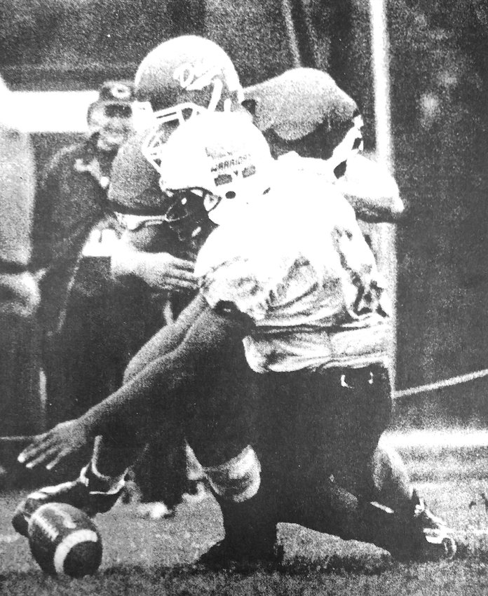 Midland quarterback Kernis Faison, front, tries to fall on a fumbled football as Dana College's Biff Schofield does the same during a October 1998 game in Blair.