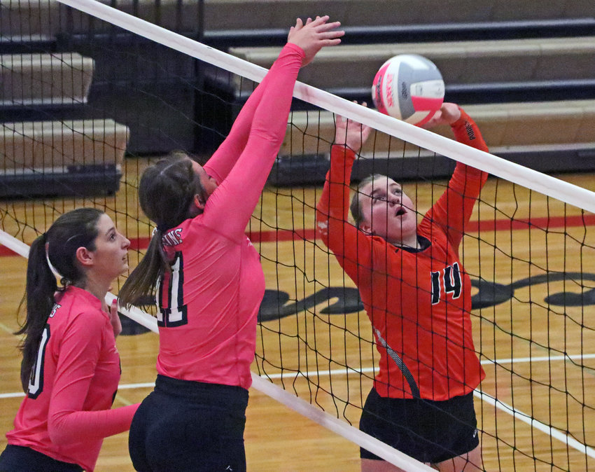 Fort Calhoun senior Rianna Wells, right, sets the ball as the Falcons' Nora Wurtz, left, and Keira Murdock play defense Tuesday at Douglas County West.