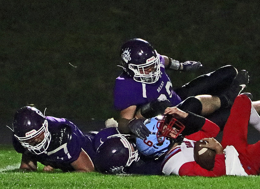 Blair defenders Lance Hume, from left, Nolan Ulrich and Cade Ulven combine to throw Ralston quarterback Harrison Acklie for a big loss Friday at Krantz Field.