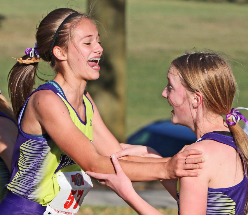 Blair cross-country runners Hailey Amandus, left, and Chloe Schrick celebrate their district finishes Thursday at Elkhorn Mount Michael.