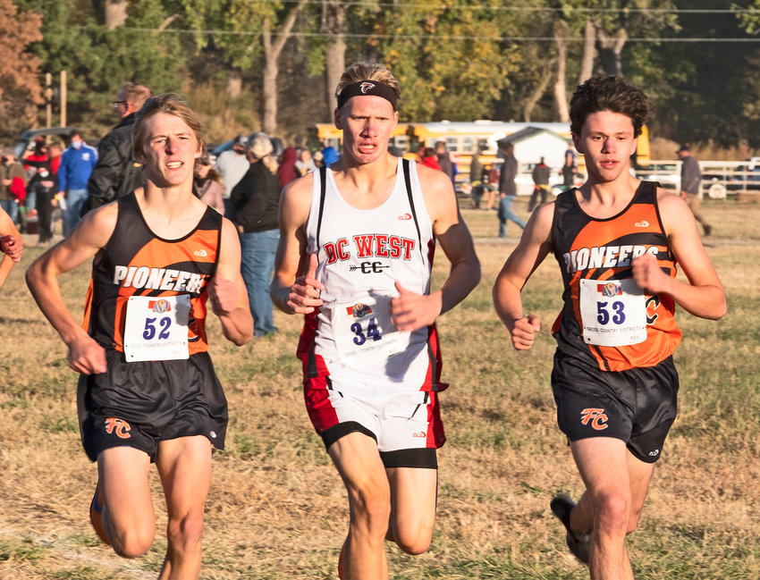 Fort Calhoun's Lance Olberding, left, and Jacob Rupp, right, run with Douglas County West's Ryan McArdle on Thursday at Sycamore Farms near Waterloo.