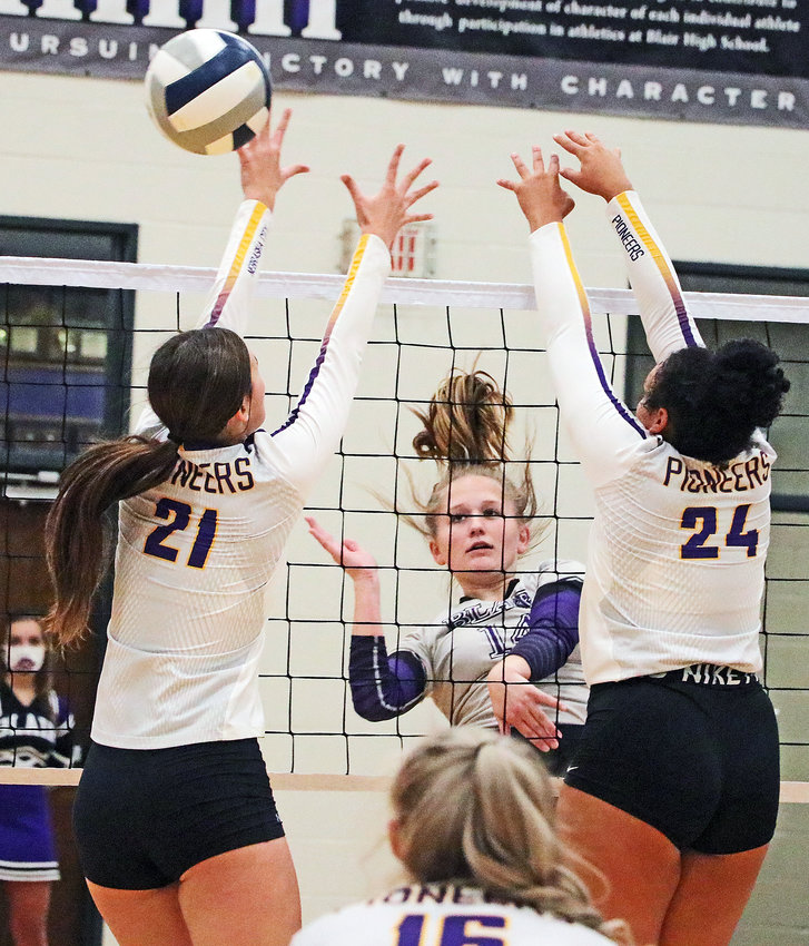 Bears senior Emma Cada, middle, spikes the ball through the block attempts of Halle Thompson, left, and Madi Mitchell on Tuesday at Blair High School.