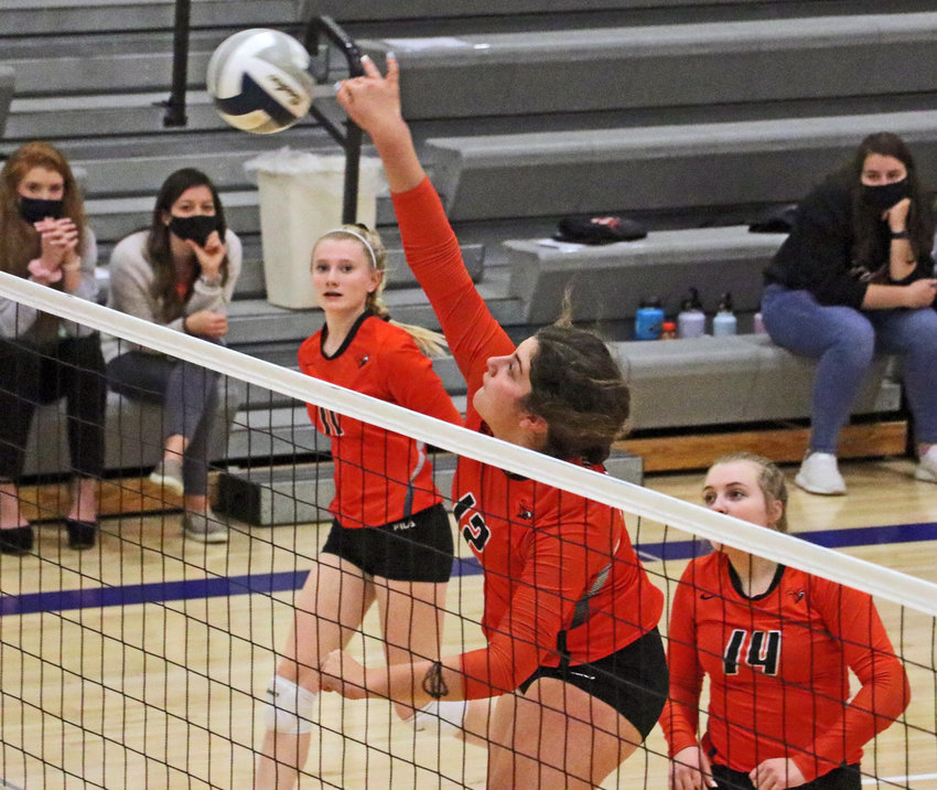 Fort Calhoun senior Alivia Cullen, middle, spikes the ball as Olivia Quinlan, left, and Rianna Wells look on Monday at Wahoo High School.