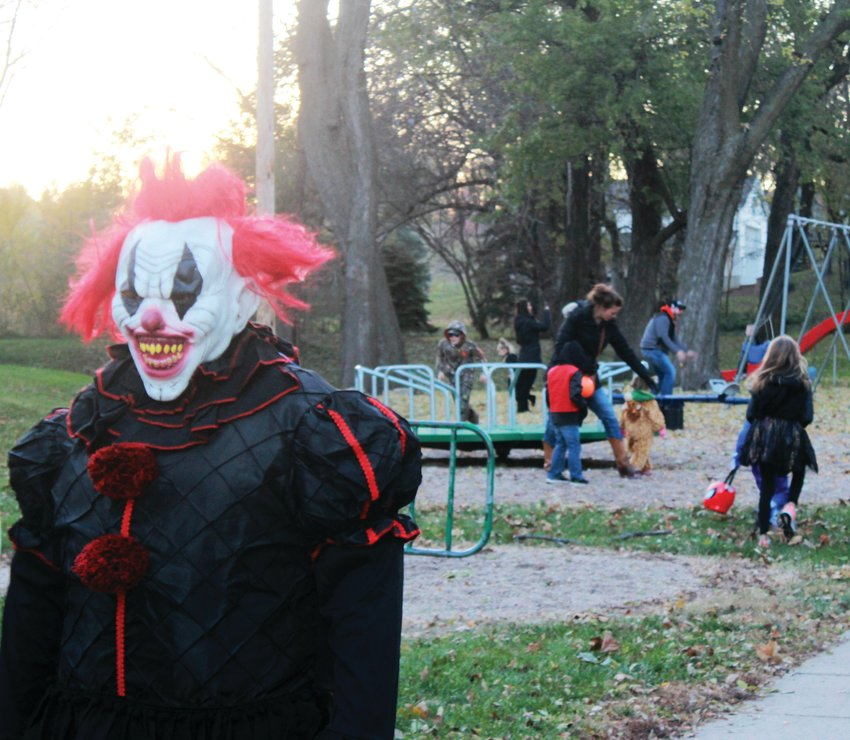 A trunk or treater dressed as a clown walks by while kids play in West Market Square Park during the Fort Calhoun Enhancement Committee's Trunk or Treat held on Halloween last year.