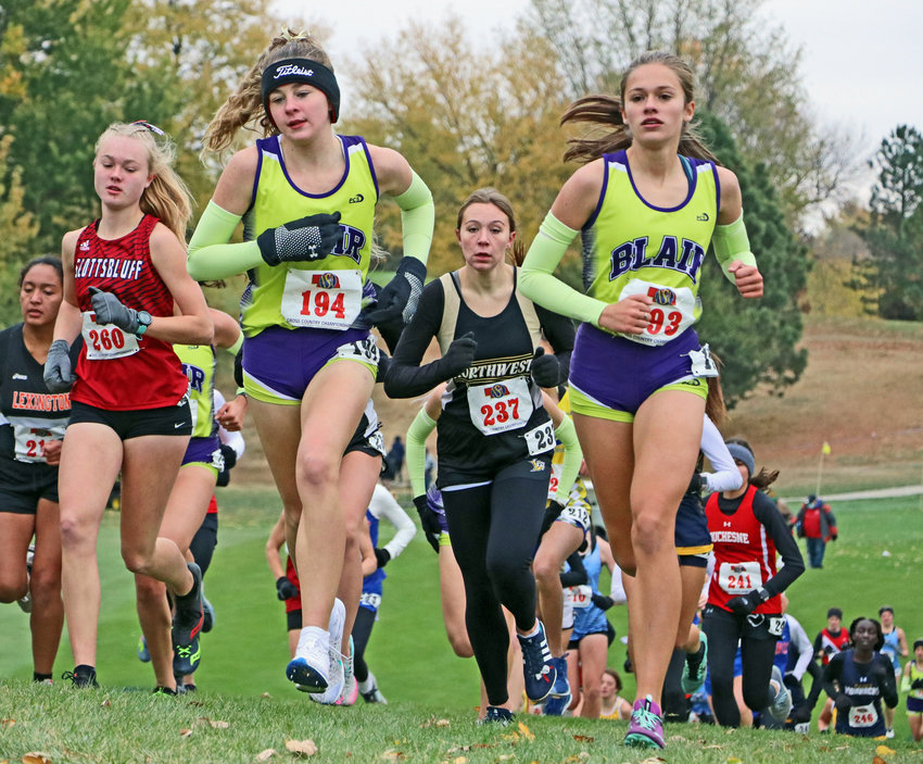 Blair runners Allie Czapla, left, and Hailey Amandus, right, run side-by-side Friday during the early stages of the Class B cross-country race at Kearney Country Club.