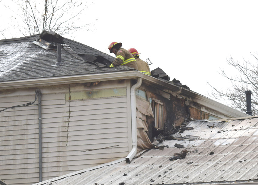 Arlington volunteer firefighters fight a rekindling of a fire at 355 N. Eighth St. in Arlington on Monday morning that started overnight.