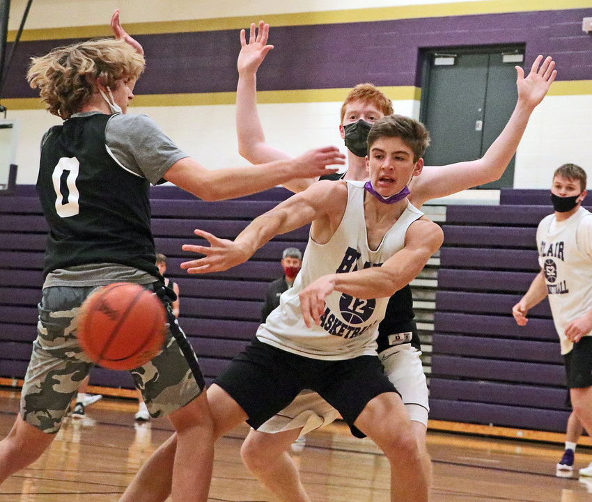 The Bears' Luke Ladwig, middle, passes the ball out from between teammates Kade Ryden, left, and Leo Clarke on Tuesday during practice at Blair High School.