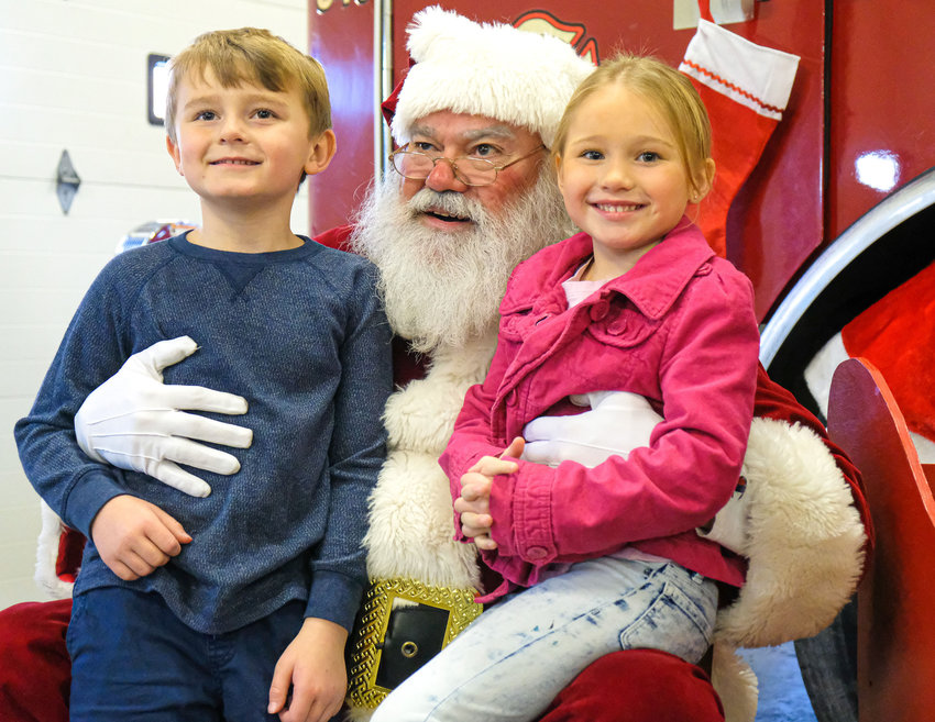 Riley and Morgan Adams sit on Santa's lap to pose for a photo at the Blair South Fire Station during the 2019 visit. This year, due to the pandemic, Santa will greet visitors from the bed of a firetruck.