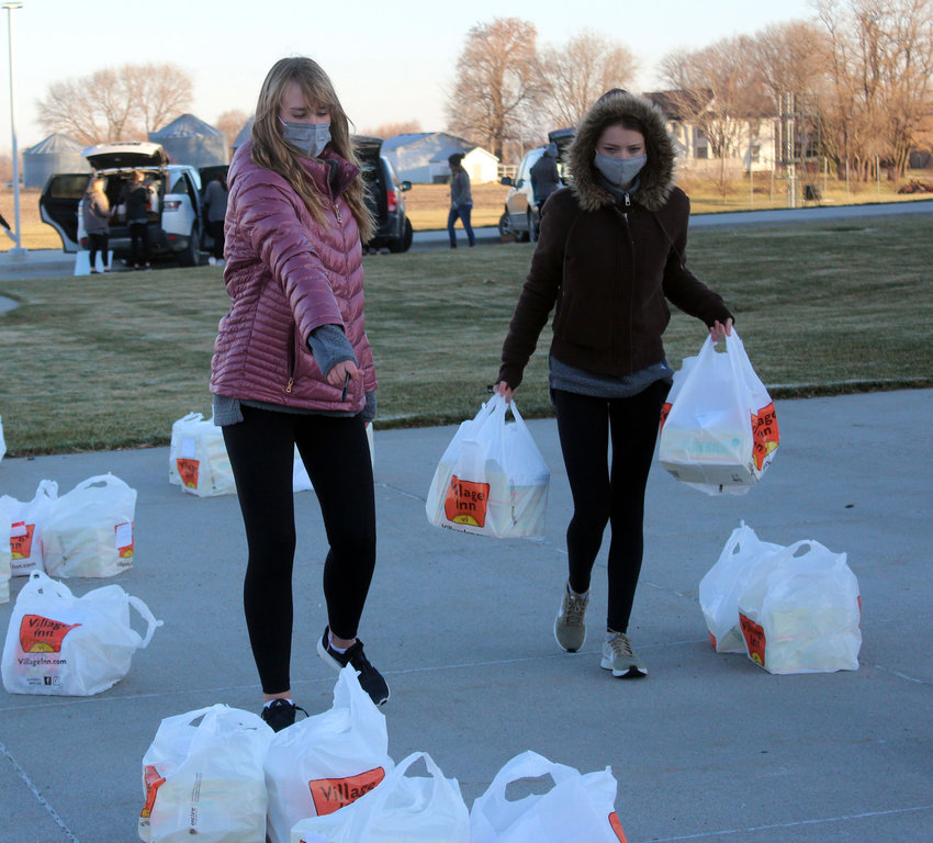 Alayna Prunty, left, and Angel Nelson walk pies to the front of Fort Calhoun Jr/Sr High School Thursday. The girls are part of the Fort Calhoun cheer team, and raised $600 in funds for the pies.