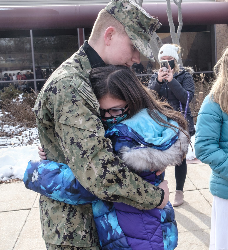 Colin Priestino holds sister Bianca Moreno.  Navy seaman Priestino surprises sister at Arbor Park School Friday afternoon during school sing-along.