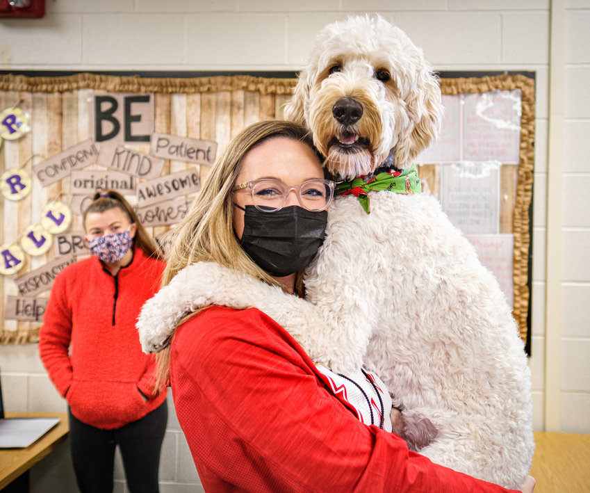 Special education teacher Monica Maly holds her 2-year-old goldendoodle Ted, who serves as a therapy dog at Blair High School.