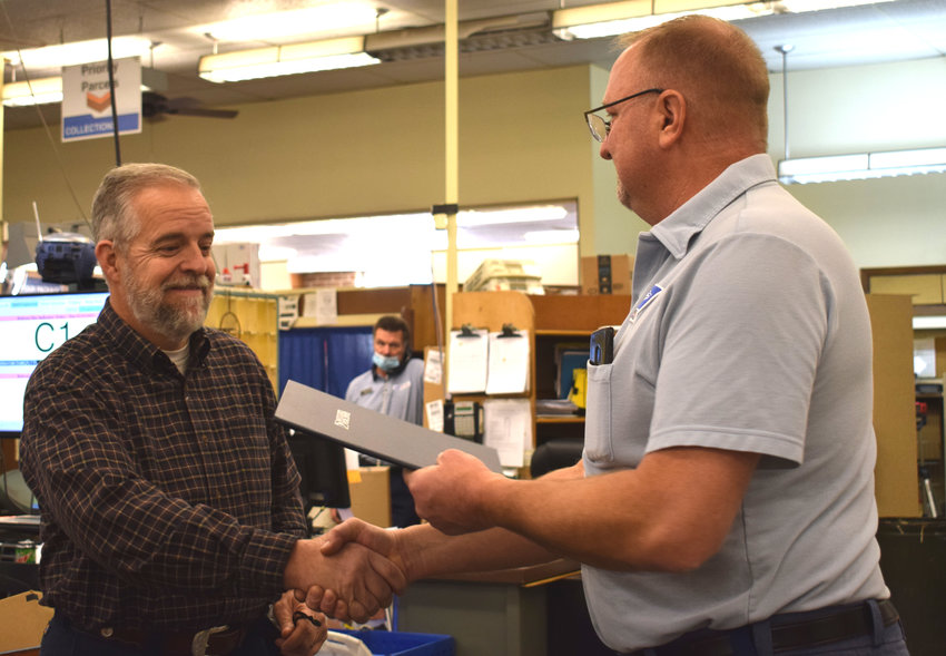 Steve Jones retired from the post office Thursday after 37 years. He received a placque from Brian Greunke, right, at a reception acknowledging his retirement.