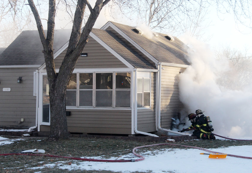 Blair firefighters Joe Maguire and Joe Leonard spray water into the basement of a house at 280 N. 22nd St. on Wednesday in Blair. Flames could be seen shooting out the basement window when firefighters arrived.