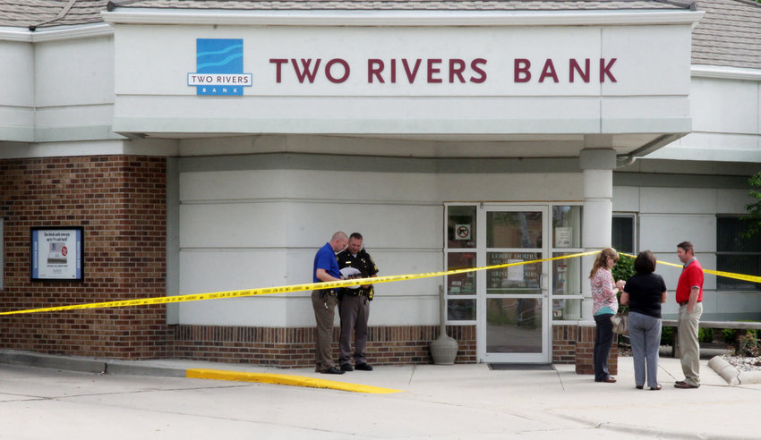 Washington County sheriff's deputies talk while three employees of the Blair branch of Two Rivers Bank wait outside the Arlington branch at 130 W. Eagle St., following an armed robbery in 2017.
