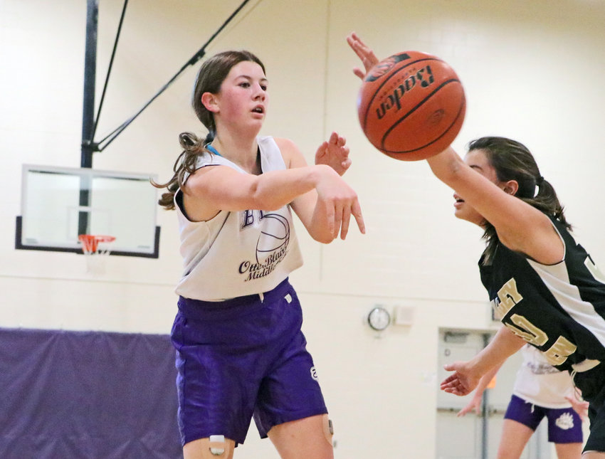 Otte Blair Middle School seventh-grader Angela Roehrs, left, throws a pass around a Elkhorn Valley View defender Thursday during the Bears' home opener. The seventh-grade girls basketball season continues through March 1 with five more home games on the schedule.
