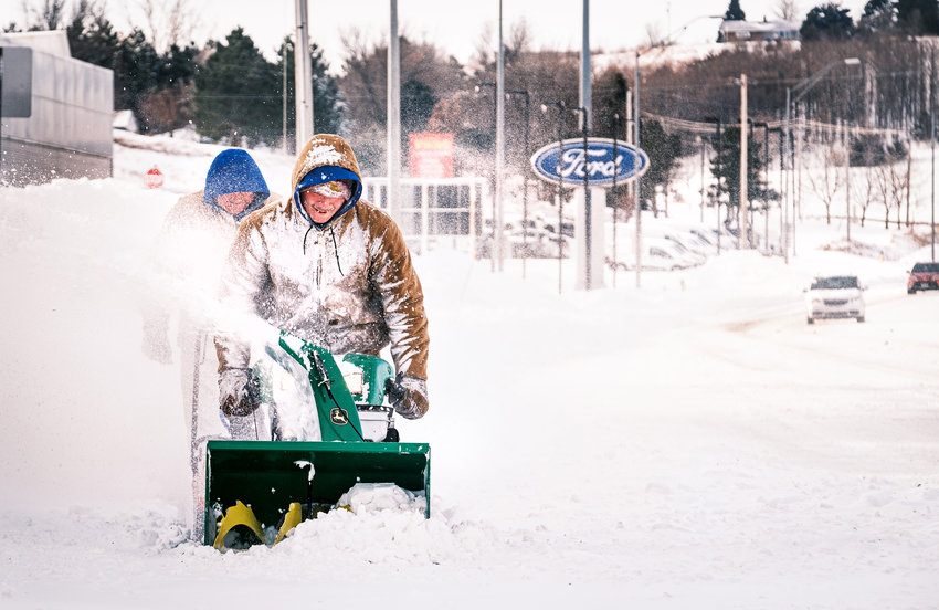 Tanner Mace and Joe Moore clear the heavy snow on the sidewalk between Woodhouse Ford and Kellie Drive on Tuesday morning. Both men work for Woodhouse Ford.
