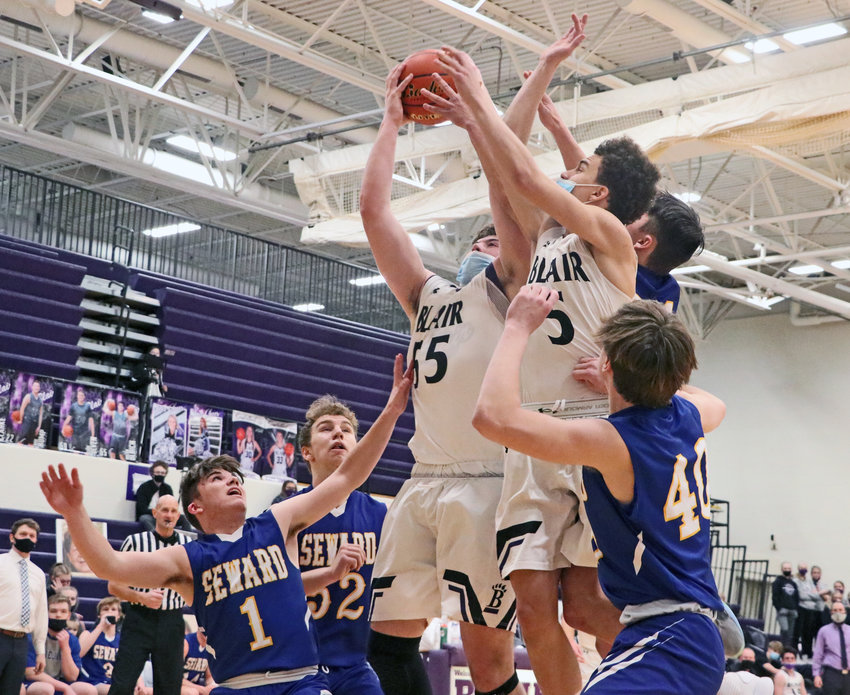 Bears senior Nolan Ulrich pulls down an offensive rebound in traffic — which includes teammate Nolan Slominski — Friday against Seward at Blair High School.