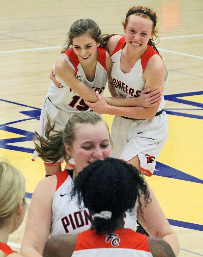 Fort Calhoun's Tess Skelton, back left, and Abbie Anderson embrace, celebrating Monday's subdistrict tournament victory at Wahoo High School. The Pioneers defeated Omaha Concordia 50-47.