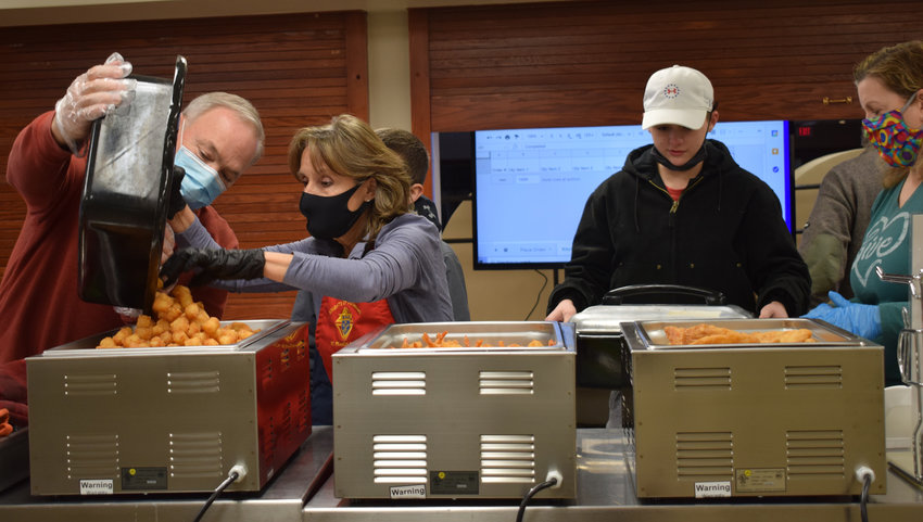 Volunteers at St. Francis Borgia Catholic Church in Blair prepare to serve fish dinners to customers through a drive-thru at the parish on Friday.