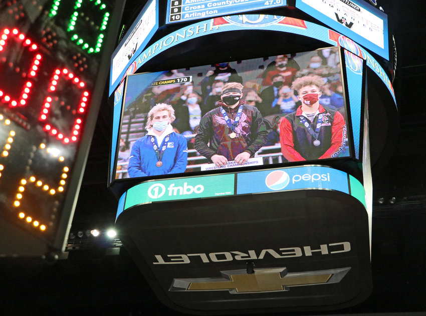 Arlington senior Josh Miller, middle, stands atop the podium with his championship bracket Saturday night on the CHI Health Center scoreboard.