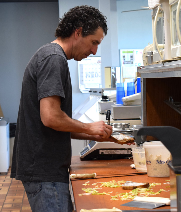 Butch's Deli owner Adam Thiel makes a sandwich behind the counter on Monday.