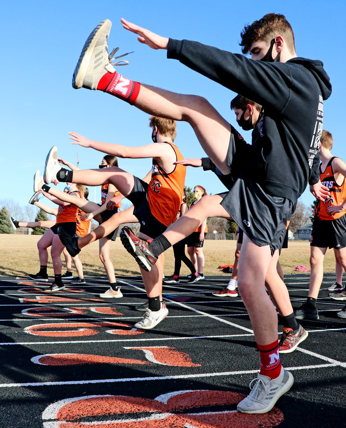Aaron Duros, front, and his Pioneer teammates stretch before track and field practice Wednesday at Fort Calhoun High School.