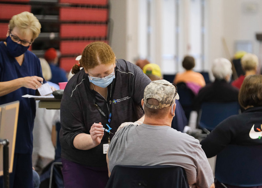 Mary Kempcke, left, prepares a vaccination card while Keala Roy administers a vaccination dose at a clinic held by Memorial Community Hospital and Health System in the Gardner-Hawks Center in Blair.