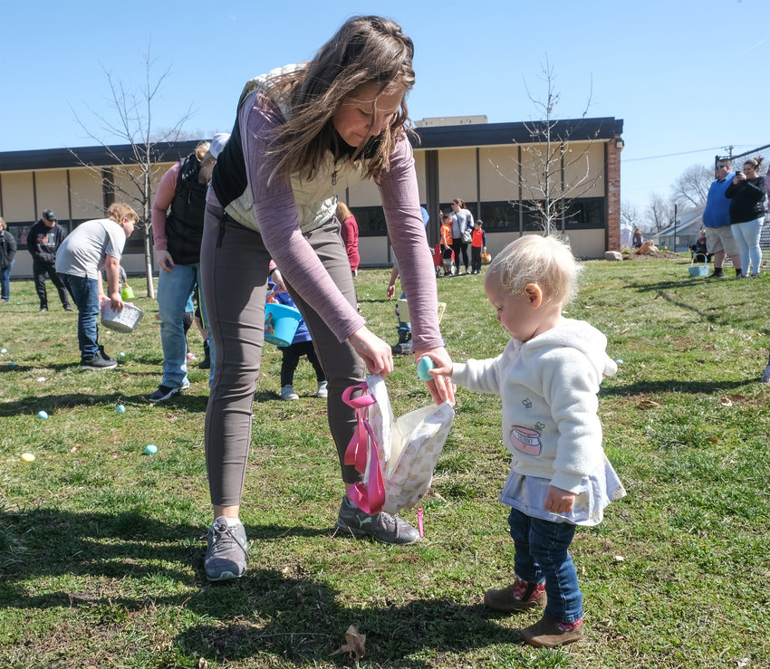 Kiah Wamberg, 7 1/2 months, is ready to drop her egg into bag her mother, Brittany, is holding Saturday during the Blair Optimist Club's annual Easter egg hunt.