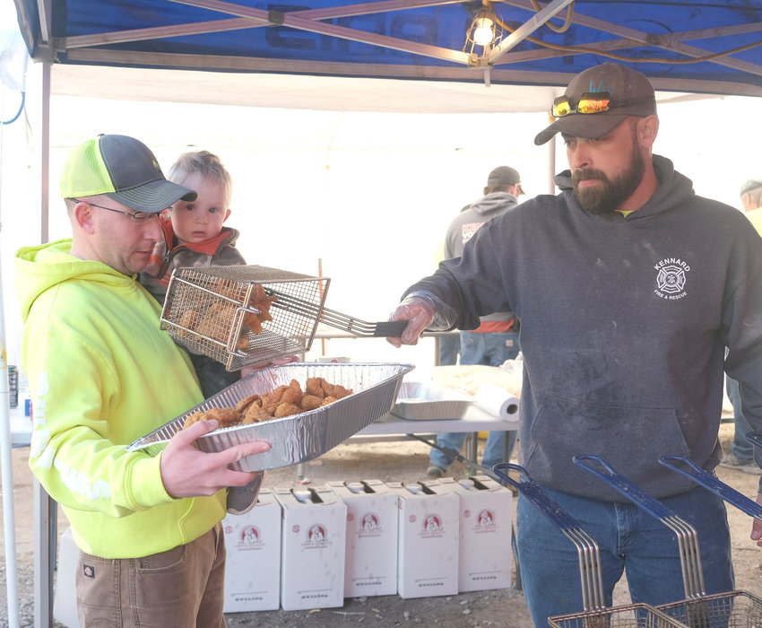 Cord Hansen, with son Cael, holds the pan steady as Chris Potter pours in a basket of piping hot fried fish Friday during the Kennard Fish Fry.