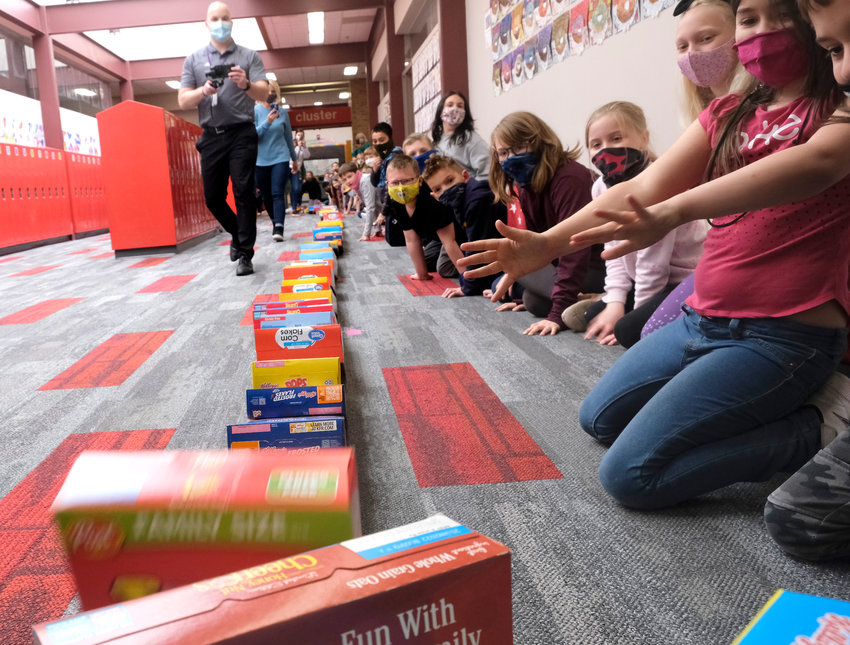 Students cheer as boxes of cereal fall in a domino effect Thursday at Arbor Park Intermediate School. The students donated 940 boxes of cereal to the Washington County Food Pantry.