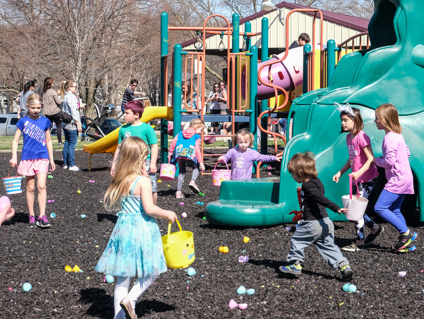 Kids search high and low for plastic easter eggs during the Arlington Egg Adventure.