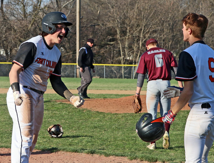 The Pioneers' Justin Myer, left, celebrates his game-ending, inside-the-park home run with Jake Seina on Thursday in Fort Calhoun.