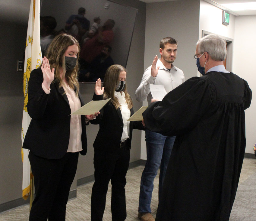 From left, Jessica Penry, Andrea Murphy, both full-time, and James Hetzler, part-time, are sworn in as Washington County Sheriff's Office deputies by Judge John E. Samson Tuesday evening.