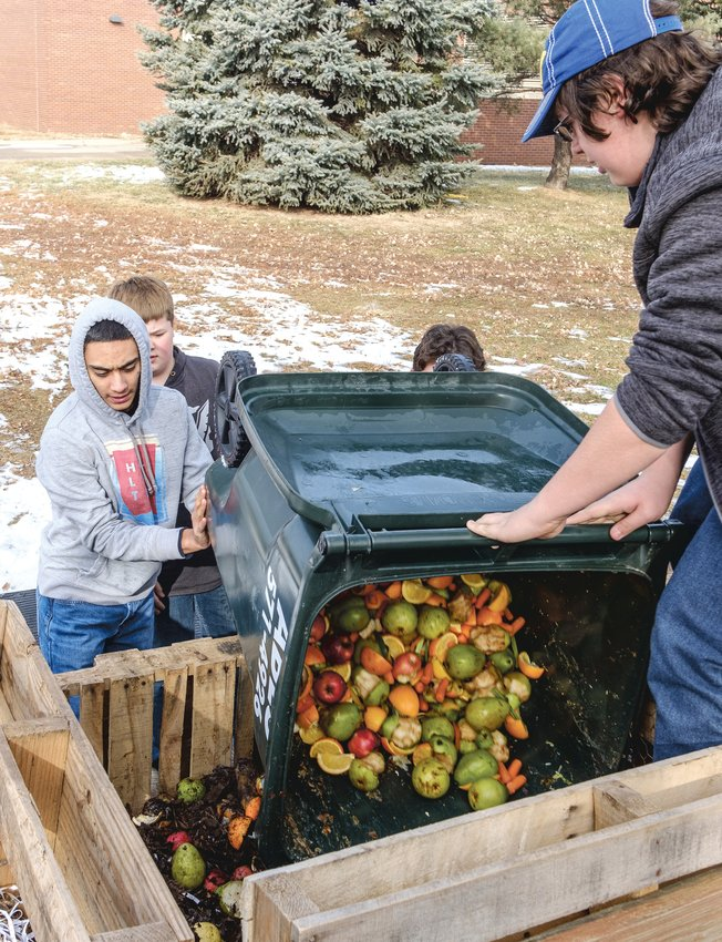 Carlos Najera-Trevizo, left, helps Logan Taullie dump leftover fruits and vegetables from school lunch onto a composting pile in 2019 at Otte Blair Middle School.