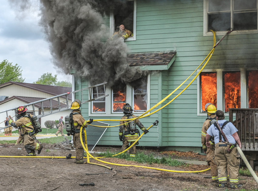 As fire spreads through the first floor, firefighters search for victims and determine how to evacuate an individual (dummy) from a second floor room during a practice burn Sunday in Fort Calhoun.