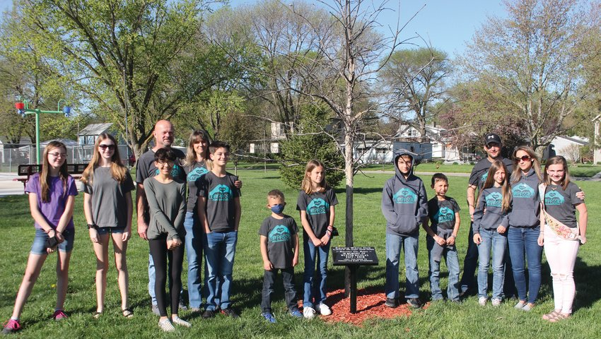 Members of Arlington Girl Scout Troop 50099 post for a photo with Weston Nicolas' family Saturday following the dedication of a tree planted in Weston's honor. Weston, 1, died in 2019. His mother, Trisha, is originally from Arlington.