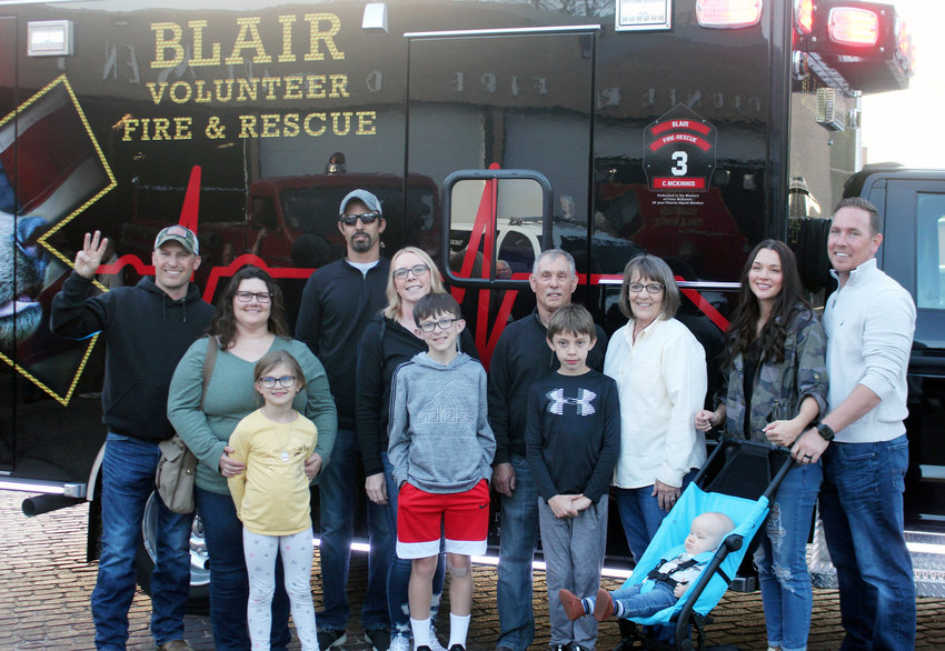 Members of the McKinnis family pose for a photo with the new Blair Rescue squad, which was dedicated in memory of Clair McKinnis, who was a charter member of the rescue squad and served 66 years with the Blair Volunteer Fire Department. BVFD received the squad Thursday night.