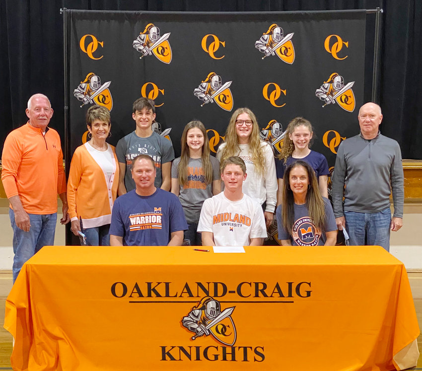 Gunnar Ray signs with Midland University for Basketball and Golf. Here he is joined by famiy members sitting from left Gus Ray, Gunnar Ray and Nikie Ray. Standing  from left: Dale Johnson, Anne Johnson, Lincoln Benne, Hilary Ray, Morgan Ray, Briar Ray and Greg Ray.