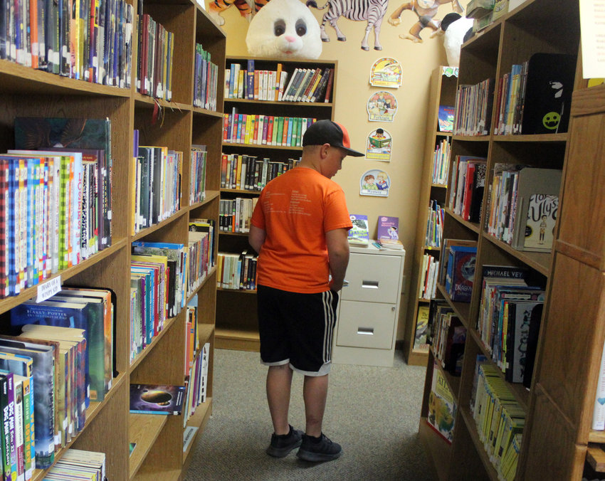 Owen Dougherty, 10, looks through an aisle at the Fort Calhoun Library after signing up for the summer reading program Wednesday afternoon. The program will run through the summer until the week before school starts in August.