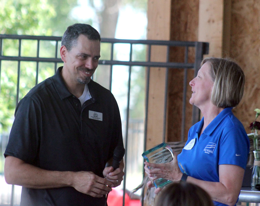 Michael Rooks, director of Gateway Development, presents an Outgoing Gateway Board of Directors award to Brandi Petersen, executive vice president of Two Rivers Bank.