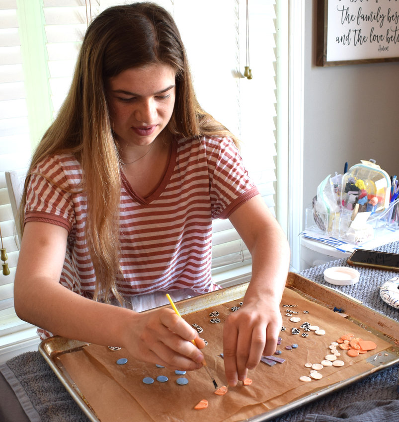 Kate Miller, a rising senior at Arlington High School, works on the earrings she makes for her company, Pure and Rose. She sells the items at Sugar Shack in Arlington and Main Street Market in Blair.