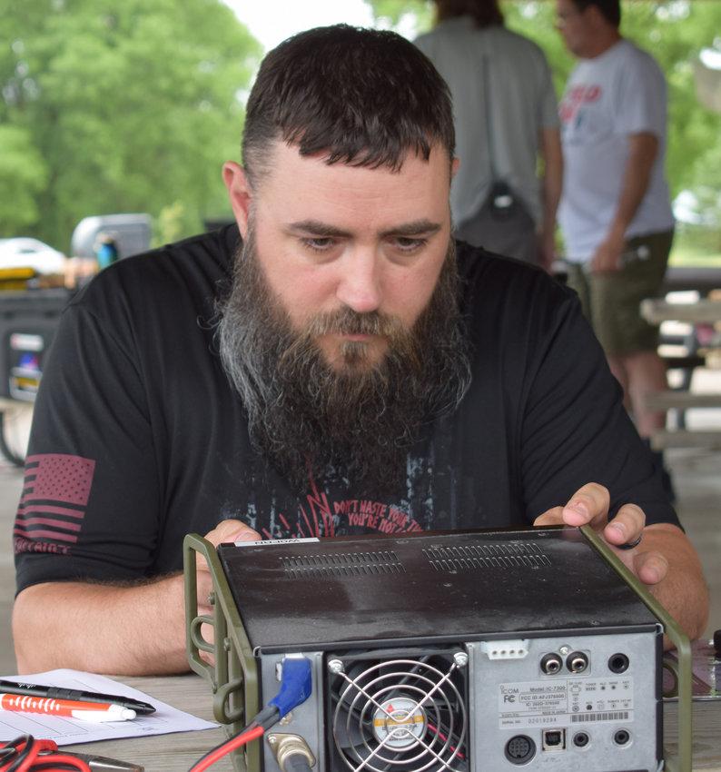 Tom Winburn of Bellevue works on his ham radio at the Amateur Radio Field Day on Saturday at Black Elk-Neihardt Park.