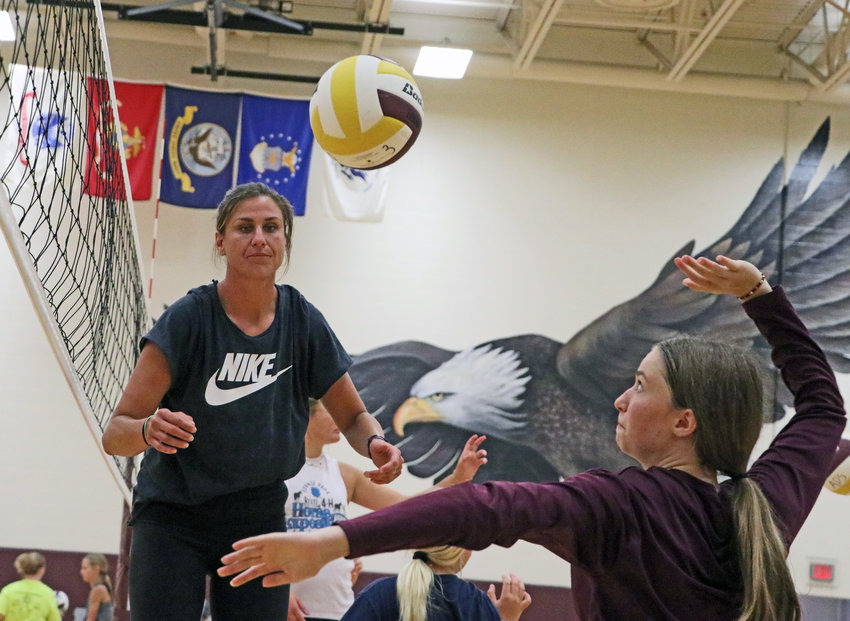 Volleyball camp instructor Brooke Delano, a former Nebraska All-American, works with eighth-grader Maddie Martens on Tuesday at Arlington High School.